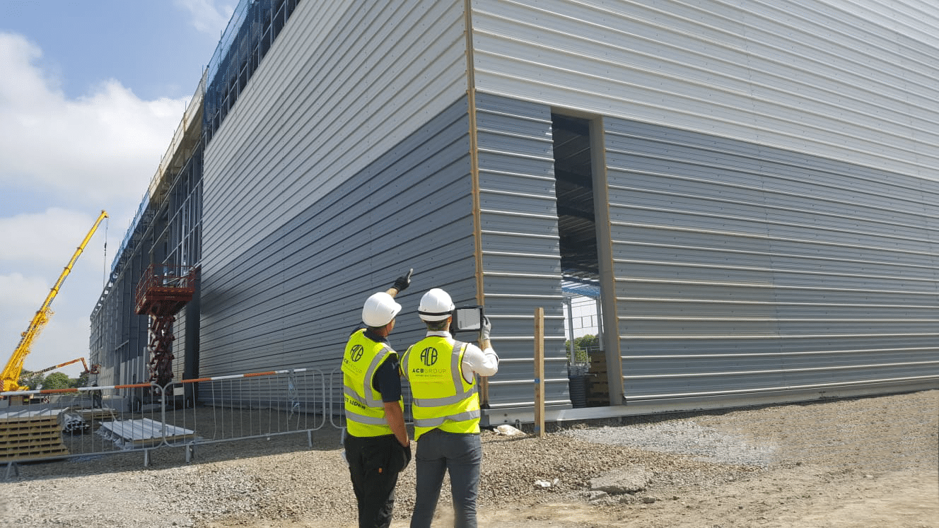 Two ACB workers examine the cladding of a building in hi-vis jackets